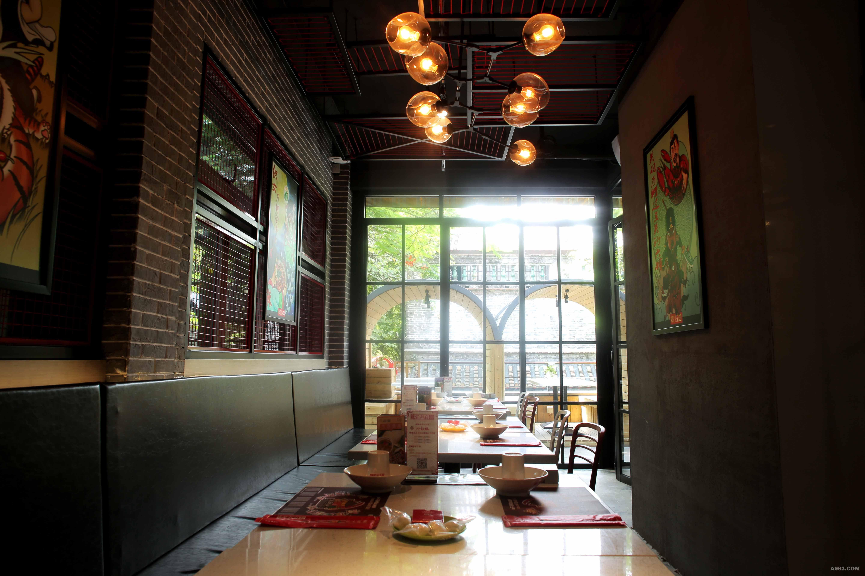 """以""""辣焦焦""""的工业风主题概念融入空间,通过铁网、机甲、清水泥、旧砖材等元素的运用衍生出独特餐饮空间。 本店建筑分为上下两层,首层在入口处设置通透铁艺造型屏风让顾客视线得以延伸,过道处与餐区之间通过铁艺屏风的规划营造空间氛围。二层设计则以包房空间为主,利用室外露台设计出半围闭的露天卡座,室内则运用落地玻璃将空间划分成独立包房。"""
